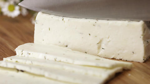 Fresh white cottage cheeze with dill being cutted with knife on cutting board Live Action