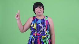 Happy young overweight Asian woman pointing up ready to party Footage