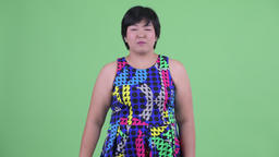 Excited young overweight Asian woman giving thumbs up ready to party Footage