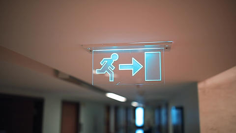 Emergency Exit sign symbol man with right arrow in hospital or office corridor Footage