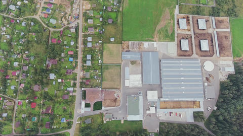 Top view above several houses surrounded by green lawns and agricultural area Footage