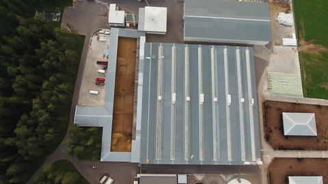 Quadcopter flies over grey roofs of modern agricultural animal farm buildings Live Action