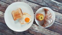 Healthy tasty breakfast: fried egg, toast, apple and croissant Footage
