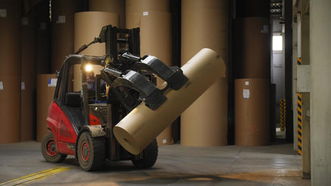 forklift loader carries packaging paper in plant warehouse Live Action