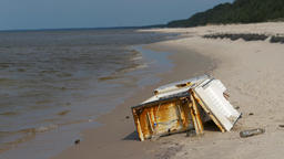 Rusty fridge on a beach. Environment pollution concept Live Action