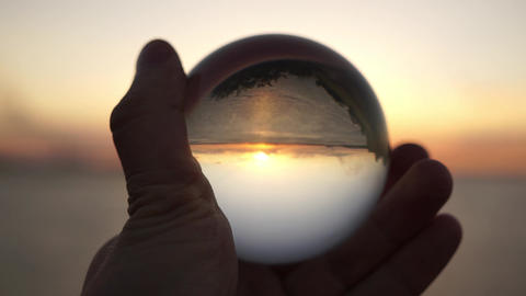 Male hand holds a glass ball on a background of sunset at sea. Dramatic Footage