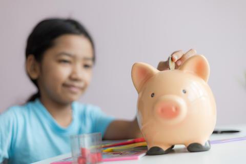 Little asian girl putting money coin into piggy bank 006 フォト