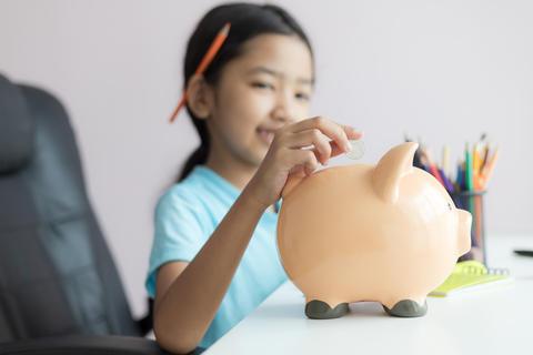 Little asian girl putting money coin into piggy bank 005 フォト