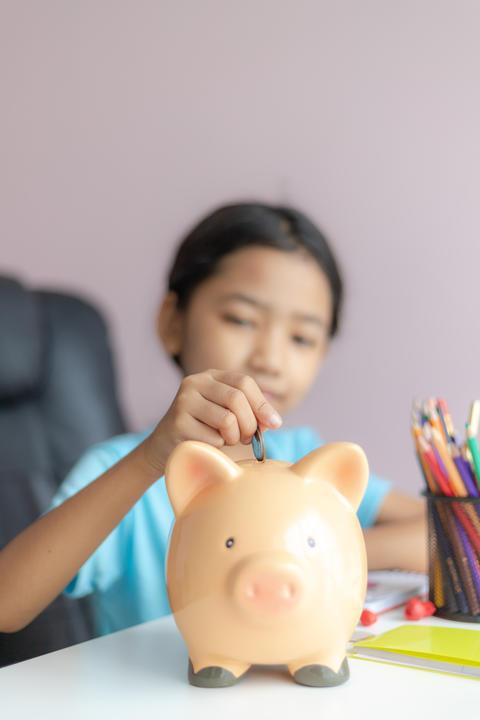Little asian girl putting money coin into piggy bank 017 フォト