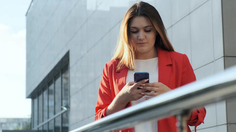 Business woman in a red jacket reads a message in a smartphone Live Action