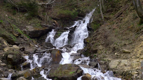 Calm waterfall flowing down in the mountain cliff in forest big rocks Footage