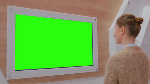 Woman looking at blank green display wall at exhibition - green screen concept Footage