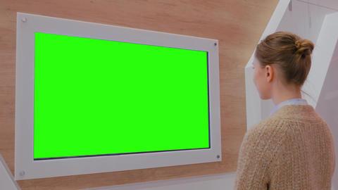 Woman looking at blank green display wall at exhibition -…, Live Action