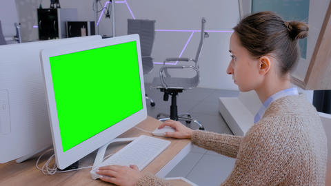 Woman looking at white monitor of desktop computer with blank green display Live Action