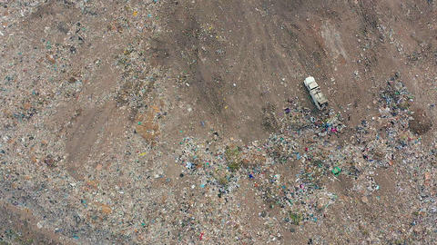The Bulldozer Compacts the Garbage on the Landfill. Wastes of Human Life. Aerial Footage