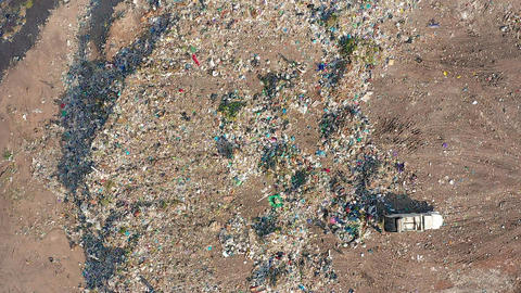 The Bulldozer Compacts the Garbage on the Landfill. Wastes of Human Life. Aerial Live Action