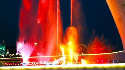 Beautiful bright fountain with illumination and flags at summer dark night Footage