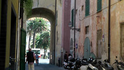 Europe Italy Liguria Albenga 025 old alleyway in downtown with a city gate at it Footage