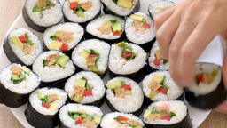 Female hands are putting sushi rolls on a plate Live Action