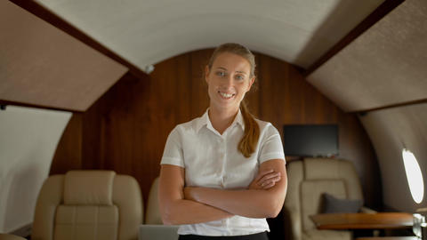 Rich business lady inside of luxury private business jet smiling and looking at Footage