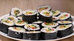 Sprinkling sushi rolls with black sesame seeds Live Action