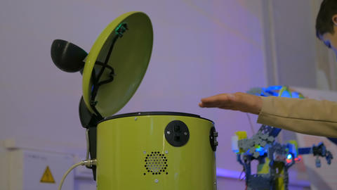 Funny yellow bucket robot trying to catch woman hand at technology exhibition Footage