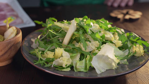 Chef adds pieces of pear to the vegetable salad with... Stock Video Footage