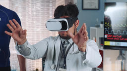 Close-up of multiracial doctor in virtual reality glasses speaking something and Footage