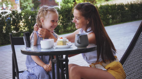 Woman and little girl embraces in cafe Live Action
