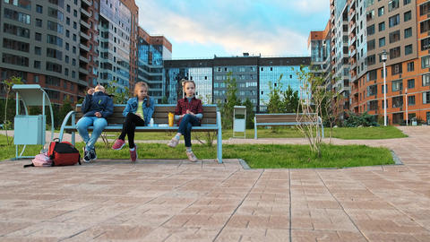 A group of children friends are sitting on a bench and eating Footage