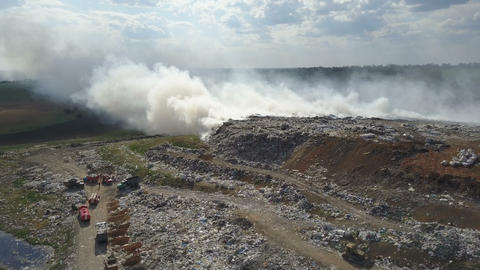 Garbage dump pollutes the environment. Strong wind rises toxic smoke of burning Live Action