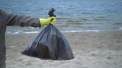 volunteer hands holding garbage bag on beach Live Action