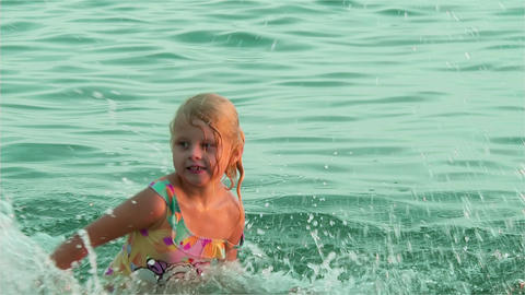 Child splashes water in the ocean water Live Action