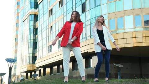 Two business women dancing in the street against the background of a business Live Action