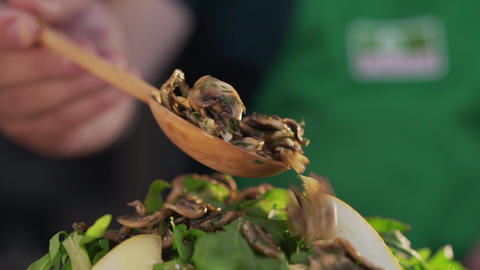 Chef adds fried mushrooms to the vegetables salad, cooking vegetarian meals Live Action