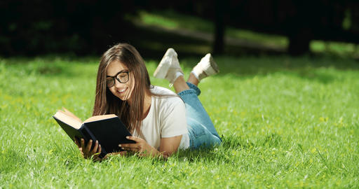 Woman Reading Book Lying on Grass Live Action