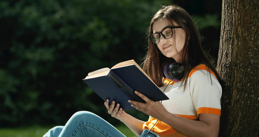 Woman with Book Relaxing in Park Live Action