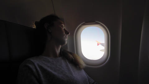 Girl at porthole in the plane. Young woman seating on passenger seat and looking Live Action