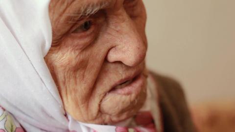 Close-up face of sad old woman. Elderly senior woman talking Footage