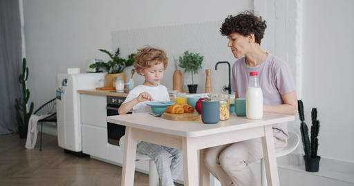 Young lady and small boy eating cereal with milk at home in kitchen smiling Footage