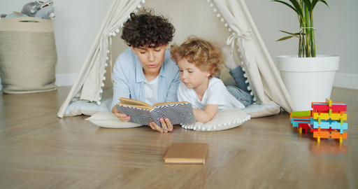 Child listening to fairy-tale while mother reading story at home in comfy tent Footage