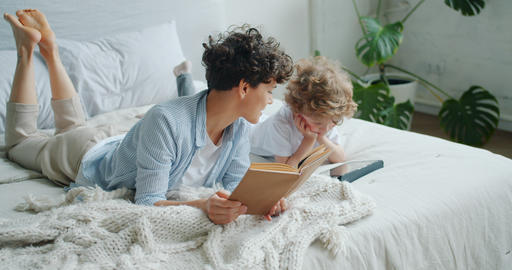 Happy family mom and child reading book and using tablet in bed at home Footage