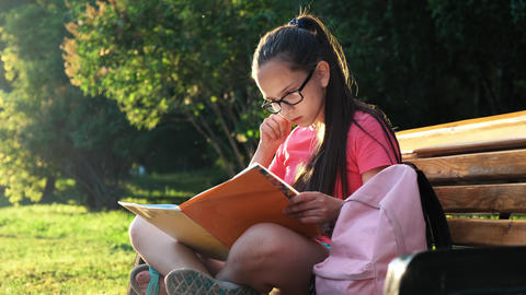 Schooling concept. A schoolgirl is sitting on a bench Stock Video Footage