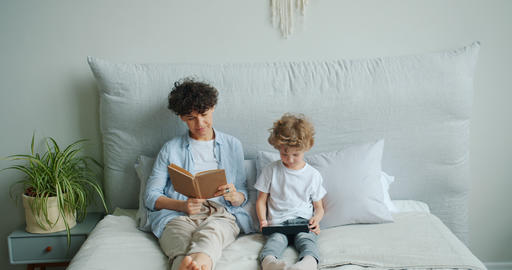 Young lady reading book while small son enjoying tablet sitting in bed at home Footage