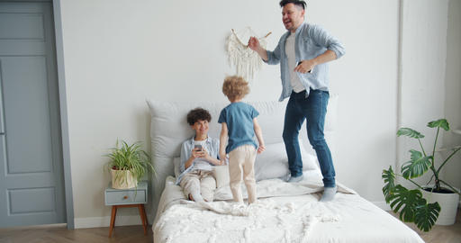 Father and son jumping on bed at home while mother using smartphone smiling Footage