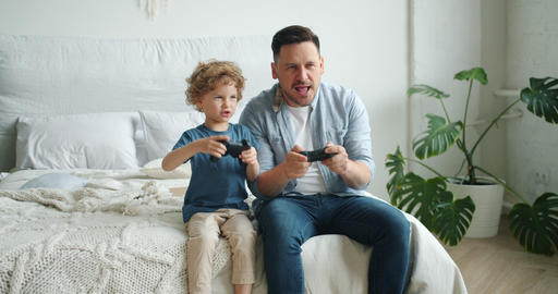 Middle-aged guy playing video game with happy child sitting on bed at home Footage