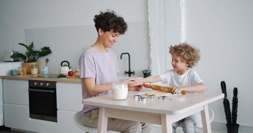 Young lady teaching small boy to roll dough cooking pastry at home in kitchen Footage