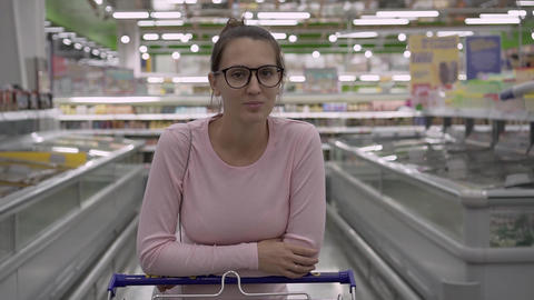 A young pregnant woman with glasses in a supermarket stands leaning on a trolley Live Action