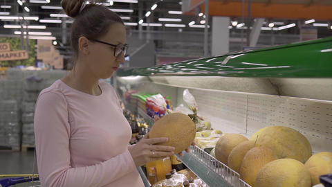 Young pregnant woman with glasses in a supermarket chooses fresh organic fruits Live Action