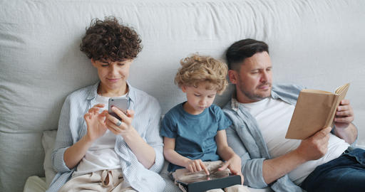 Mother using smartphone son holding tablet father reading book in bed at home Footage